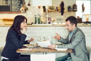 Side view of businessman with female colleague discussing paperwork at restaurant tableの写真素材 [FYI02134136]