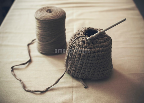 Half-finished woolen purse with spool on tableの写真素材 [FYI02134158]