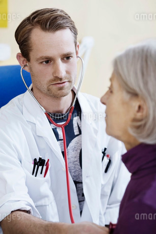 Male doctor checking senior woman's heart with stethoscope in clinicの写真素材 [FYI02134196]