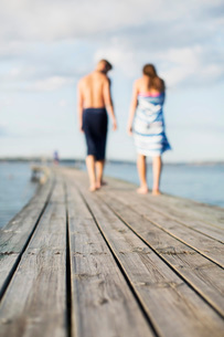 Couple wrapped in towels walking on wooden pierの写真素材 [FYI02134330]