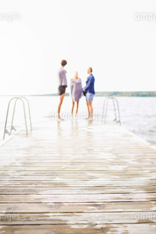 Friends wrapped in towels standing at the edge of boardwalk against clear skyの写真素材 [FYI02134666]