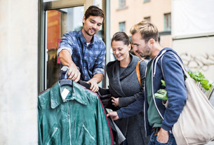 Friends shopping for jackets at clothing storeの写真素材 [FYI02134729]