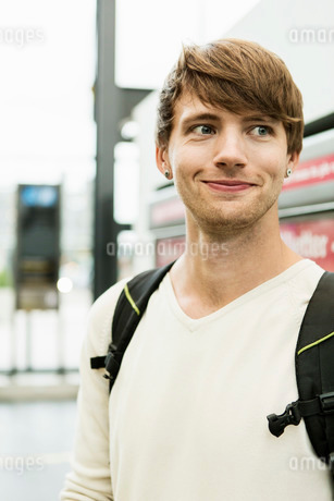 Smiling young man looking away while standing at railroad stationの写真素材 [FYI02134847]