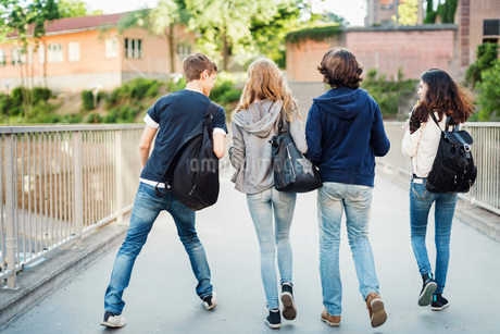 Rear view of teenagers walking on bridge in cityの写真素材 [FYI02134864]