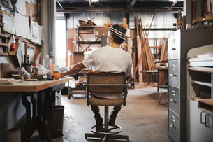 Rear view of carpenter sitting on chair at workshopの写真素材 [FYI02134975]