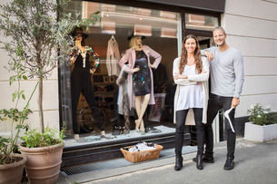 Portrait of smiling owner with female worker standing in front of clothing storeの写真素材 [FYI02135005]
