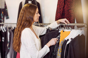Female sales person arranging cloths in clothing storeの写真素材 [FYI02135088]