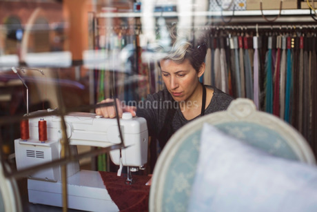 View of tailor working in studio through glass wallの写真素材 [FYI02135121]