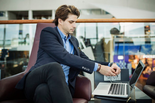Businessman connecting plug to laptop at airport lobbyの写真素材 [FYI02135240]