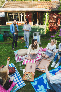 Happy multi-ethnic friends having pizza in lawn during summer partyの写真素材 [FYI02135316]