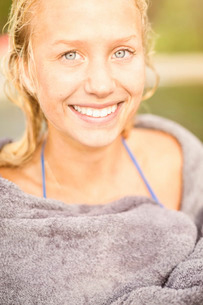 Portrait of smiling young woman wrapped in towel outdoorsの写真素材 [FYI02135340]