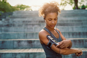 Woman using smart phone armband while exercisingの写真素材 [FYI02135533]