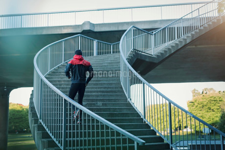 Rear view of man running on staircaseの写真素材 [FYI02135585]