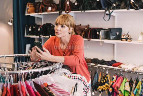 Woman holding smart phone while leaning on clothes rack at thrift storeの写真素材 [FYI02135630]