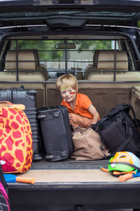 Boy sitting with luggage in car trunkの写真素材 [FYI02135753]
