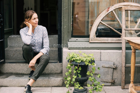 Thoughtful female owner sitting on steps at storeの写真素材 [FYI02135914]