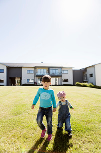 Full length portrait of siblings holding hands while walking at lawn outside house against clear skyの写真素材 [FYI02135977]