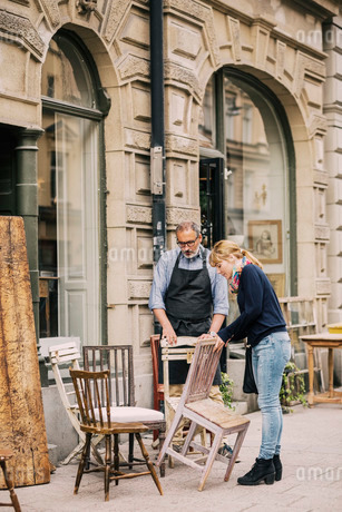 Retailer assisting customer in choosing chair outside antique shopの写真素材 [FYI02136053]