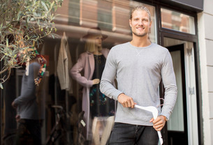 Portrait of smiling owner holding coathanger while standing outside clothing storeの写真素材 [FYI02136157]