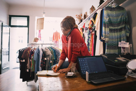 Woman writing in diary while talking on smart phone at storeの写真素材 [FYI02136348]