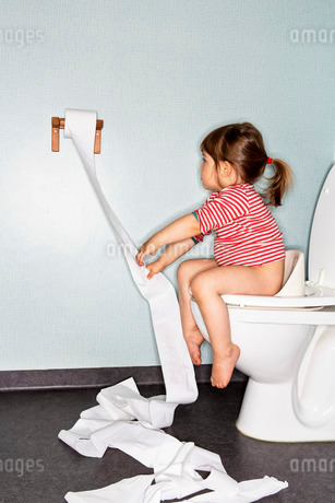 Side view of girl removing paper while sitting on toiletの写真素材 [FYI02136395]