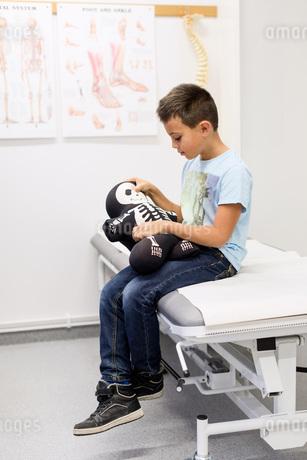 Boy holding skeleton stuffed toy on examination table at orthopedic clinicの写真素材 [FYI02136398]