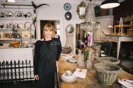 Portrait of confident female owner standing by table in antique storeの写真素材 [FYI02136572]