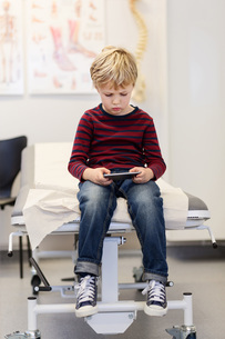Boy using smart phone on examination table in orthopedic clinicの写真素材 [FYI02136746]