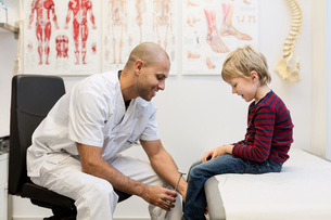 Male doctor checking knee reflexes of boy at orthopedic clinicの写真素材 [FYI02136807]