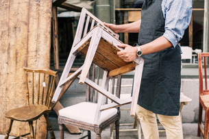 Midsection of man holding chair while standing against storeの写真素材 [FYI02136816]