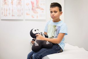 Portrait of boy holding skeleton stuffed toy on examination table at orthopedic clinicの写真素材 [FYI02136817]