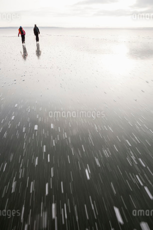 Rear view of father and daughter ice-skating on frozen lakeの写真素材 [FYI02136822]