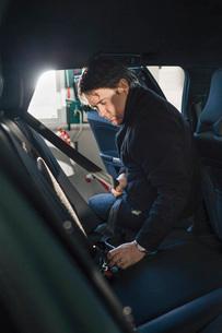 Mechanic repairing car seat belt in auto repair shopの写真素材 [FYI02136838]