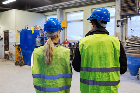 Rear view of male and female workers in protective workwear at factoryの写真素材 [FYI02136954]