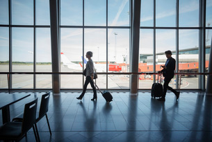 Side view of business people walking with luggage at airportの写真素材 [FYI02136962]