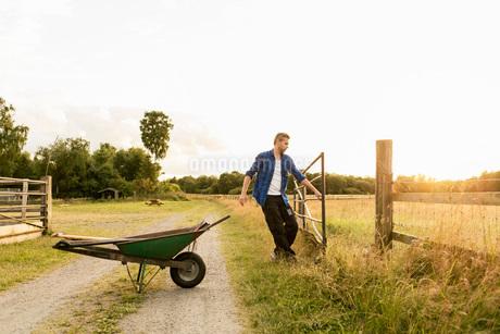 Man opening gate by wheelbarrow on dirt road against sky at farmの写真素材 [FYI02136965]