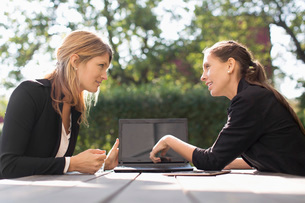 Businesswoman discussing with female colleague through laptop at outdoor cafeの写真素材 [FYI02136972]