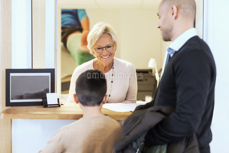 Smiling female receptionist attending family at counter in orthopedic clinicの写真素材 [FYI02136973]