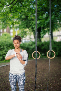 Woman using smart watch standing against gymnastic rings in parkの写真素材 [FYI02136985]