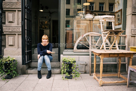 Female owner sitting on steps of antique shopの写真素材 [FYI02137000]