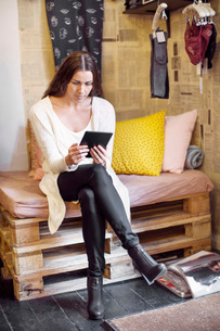 Female owner using digital tablet at clothing storeの写真素材 [FYI02137008]
