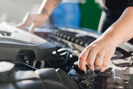 Cropped image of female mechanic opening car coolantの写真素材 [FYI02137033]