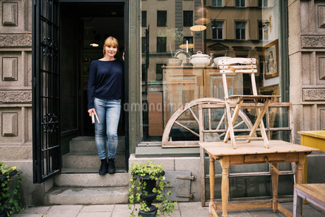 Female owner standing on entrance of antique shopの写真素材 [FYI02137039]