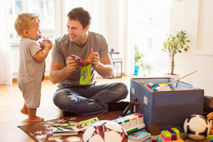 Smiling father showing toy to baby boy at homeの写真素材 [FYI02137040]