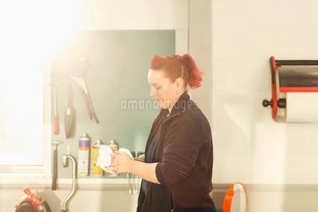 Side view of female mechanic washing hands in auto repair shopの写真素材 [FYI02137071]
