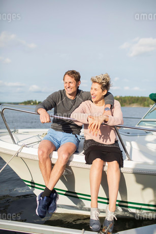 Happy couple sitting on yacht against skyの写真素材 [FYI02137121]