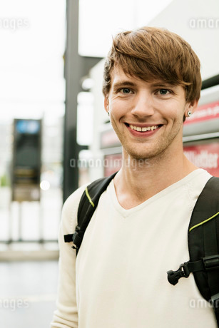 Portrait of smiling young man standing at railroad stationの写真素材 [FYI02137147]