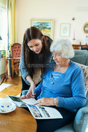 Grandmother and granddaughter reading magazine together in living roomの写真素材 [FYI02137166]