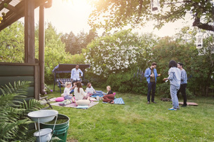 Multi-ethnic friends gossiping while having food in lawn during summer partyの写真素材 [FYI02137168]