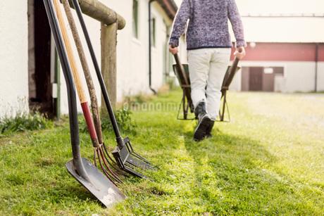 Work tools arranged by barn while woman pushing wheelbarrow at farmの写真素材 [FYI02137203]